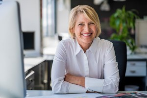 A photo of happy mature businesswoman sitting at desk. Portrait of female professional is in office. Smiling executive is in formals at workplace.