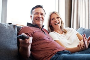 Shot of a mature couple watching tv in their living room
